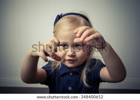 Adorable toddler girl looking strange in front of the camera. - stock photo
