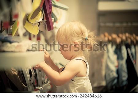 Adorable toddler girl make shopping. Choose clothes. Good leisure - stock photo