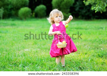 Adorable toddler girl  playing with Easter eggs s in a sunny garden - stock photo