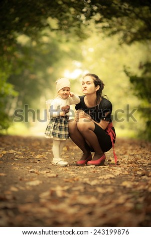 Adorable toddler girl playing with Mom in the park. Autumn. Magic beauty natural back light - stock photo