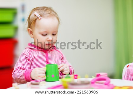 Adorable toddler girl playing with toys at home or daycare place - stock photo