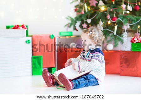 Adorable toddler girl reading a book sitting under a beautiful Christmas tree - stock photo