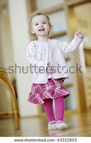 Adorable toddler girl running and laughing indoors