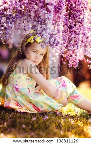 Adorable toddler girl sitting under blooming wisteria vine at sunny spring day. Kid and flower. - stock photo