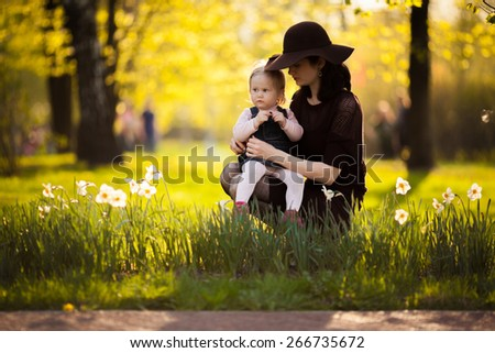 Adorable toddler girl touching her Mom in the park. Eyes closed. Summer Colorful natural light. Last things in hat - stock photo
