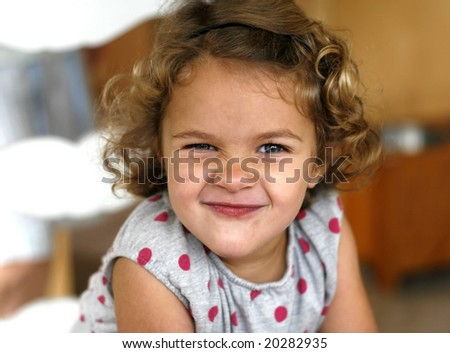 adorable toddler girl with curly hair, scrunching nose - stock photo