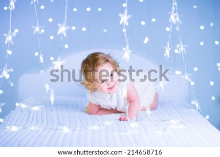 Adorable toddler girl with curly hair wearing a beautiful white dress playing in a bedroom with Christmas lights