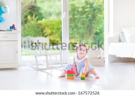 Adorable toddler girl with curly hair wearing a blue dress playing in a white sunny bedroom with a big window with garden view - stock photo