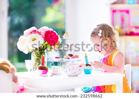 Adorable toddler girl with curly hair wearing a colorful dress on her birthday playing tea party with a doll, toy dishes, cup cakes and muffins in a sunny room with window  - stock photo