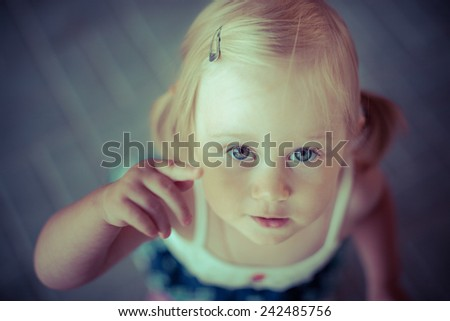 Adorable toddler girl with looking directly at the camera. Shoot from above. Wood background. Arm near the eye. - stock photo