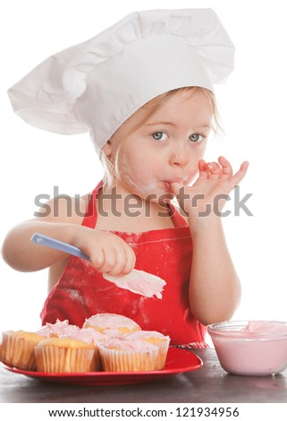 Adorable toddler in Chef's hat and red apron frosting cupcakes.  Isolated on white. - stock photo
