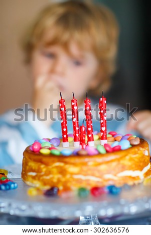 Adorable toddler kid celebrating his birthday and blowing candles on homemade baked cake, indoor. Birthday party for kids. Focus on cake - stock photo
