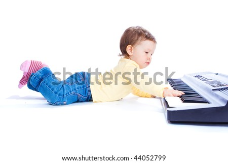 Adorable toddler lying and playing piano, isolated - stock photo