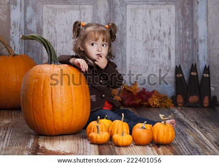 Adorable toddler sitting next to giant pumpkins and other autumn decor.