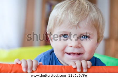 Adorable toddler with blue eyes and blond hair indoor - stock photo