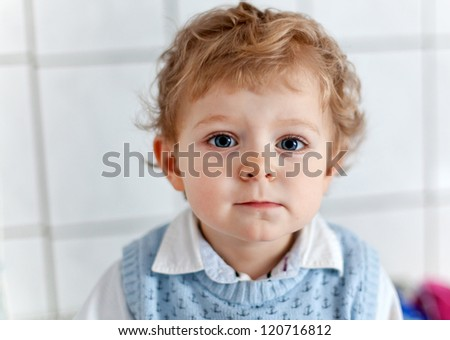 Adorable toddler with blue eyes and blond hair indoor waiting at doctor room - stock photo