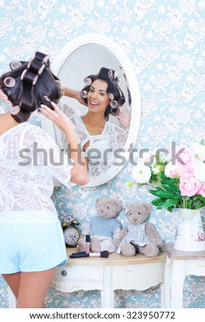 Adorable trendy woman posing in front of a mirror in hair curlers