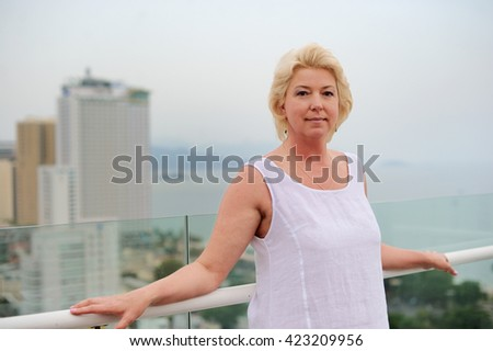 Adorable woman  on the balcony enjoing scenic view on the big city and sea - stock photo