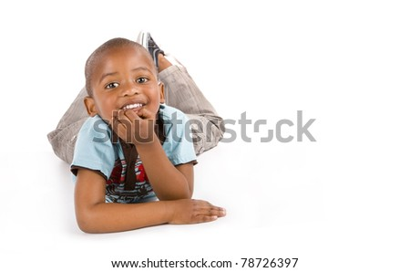 Adorable 3 year old black or African American boy with a big smile lying on the floor, space for your text. - stock photo