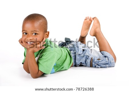 Adorable 3 year old black or African American boy with a big smile lying on the floor with his feet up looking at you - stock photo