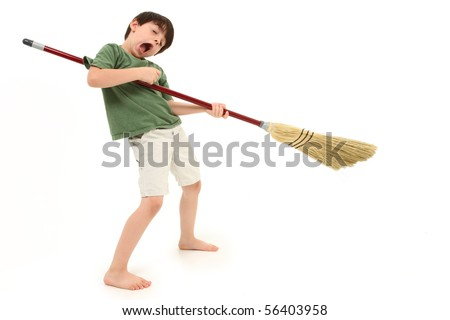 Adorable 7 year old boy child doing chores and playing air guitar with broom. - stock photo