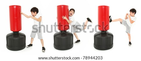 Adorable 8 year old boy practicing kicks and punches with a free standing heavy bag over white. - stock photo