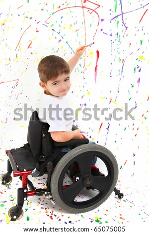 Adorable 2 year old child with wheelchair painting on floor. - stock photo