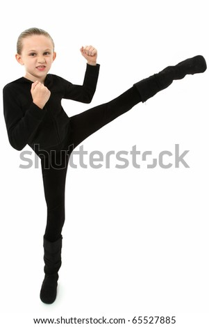 Adorable 7 year old girl in black demonstrating a martial arts kick over white background. - stock photo