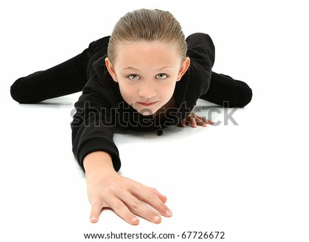 Adorable 7 year old girl in black suit crawling on white floor. - stock photo