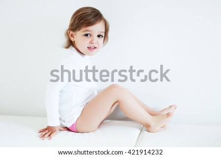 Adorable 2 year old girl sitting barefoot at home - stock photo