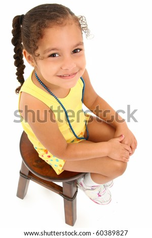 Adorable 3 year old hispanic african american girl sitting on stool over white background. - stock photo