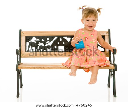 Adorable 1 year old toddler girl with pigtails in her hair. Sitting on a park bench and holding a blue cup she is just learning to drink from. Isolated on white.