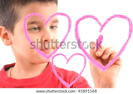 Adorable 6 years old boy painting pink hearts on glass. White background high resolution studio image  focused at his hand, face out of focus. - stock photo