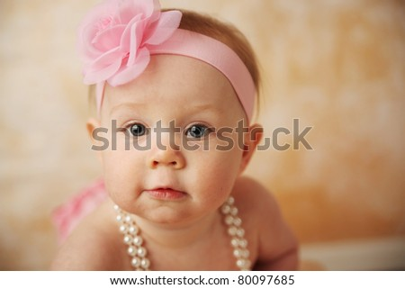 Adorable young baby girl wearing a vintage pearl necklace and pink rose headband - stock photo