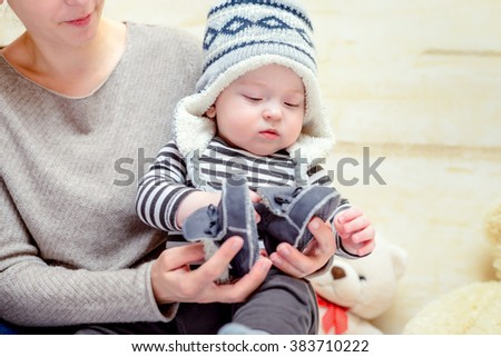 Adorable young baby in a blue and white knitted winter outfit sitting on his mothers lap as she dresses him with matching blue shoes or booties - stock photo