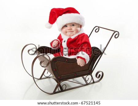 Adorable young baby wearing a santa claus suit and hat sitting in a metal Christmas snow sleigh - stock photo