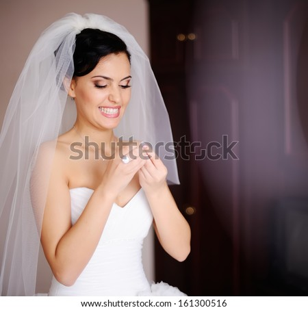 Adorable young  bride is getting ready in the morning at home. - stock photo