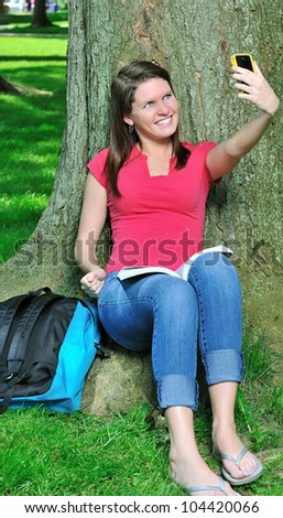 Adorable young Caucasian female student sitting in the shade of a tree taking a picture of herself with a cell phone camera - backpack next to her and book on her lap - stock photo