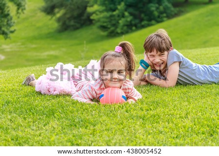 Adorable young children, boy an girl in the park. On warm summer day during school holidays. Kids dreaming and smiling. - stock photo