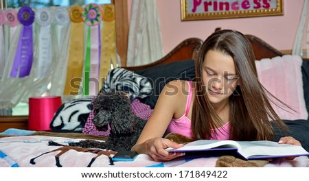 Adorable young girl laying on her bed in her bedroom - wearing pink pajamas - her small black dog on bed with her as she reads a textbook - stock photo
