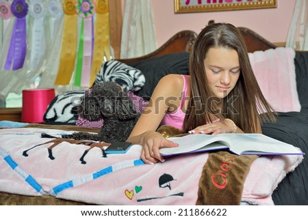 Adorable young girl laying on her bed in her bedroom - wearing pink pajamas - her small black dog on bed with her as she studies from textbook - stock photo