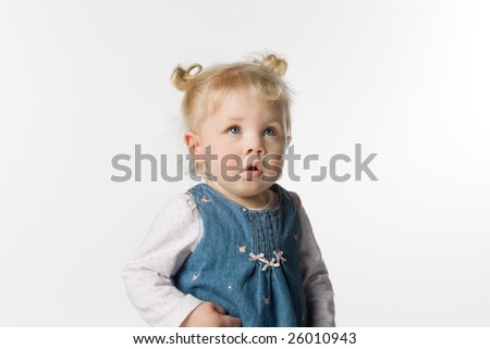 Adorable young girl of about one year old looking up. She has pigtails. On a white background.