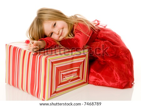 Adorable young girl, smiling and holding a lollipop while leaning over her big present. Kids paradise, two good things in one -- candy and presents! - stock photo