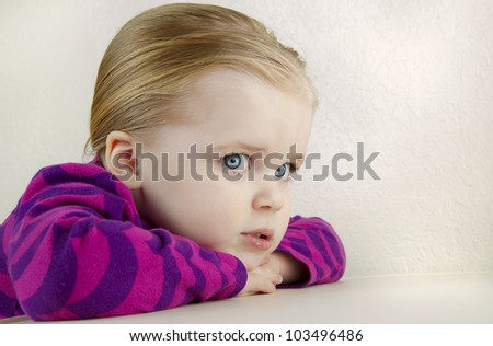 Adorable young girl with resting her head on her folded hands against a white background.