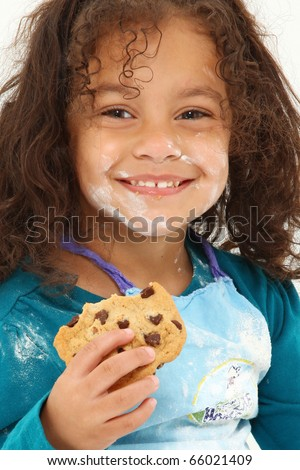Adorable young Hispanic girl covered in baking flour eating a chocolate chip cookie over white. - stock photo