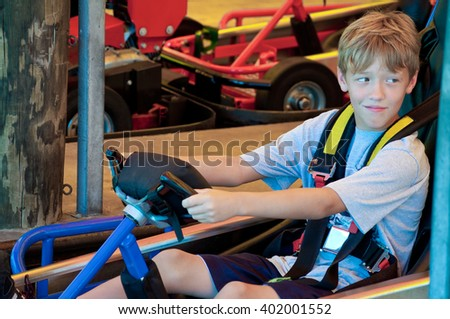 Adorable young kid on a go cart at an amusement part looking sideways. - stock photo