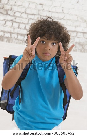 Adorable young kid ready for school with his bag - stock photo