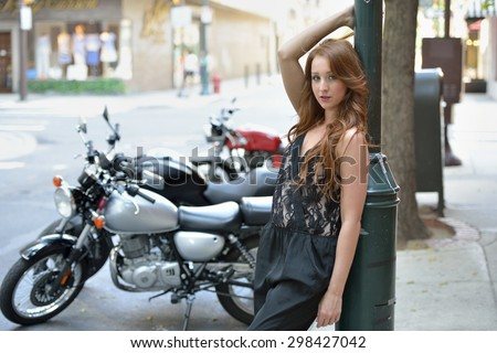 Adorable young red haired woman in black romper poses on city street - in front of motorcycles and next to light pole - stock photo