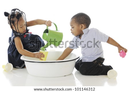 Adorable, young siblings busy in a tub of water and water toys.  On a white background. - stock photo