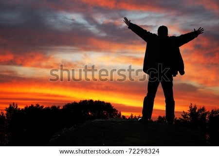 Adoration of heaven. Silhouette of the man with hands upwards, on a sunset - stock photo